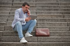 Бизнесмен с таблеткой на предпосылке лестниц Работник говоря на телефоне Концепция деловой беседы скопируйте космос Стоковая Фотография