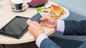 Бизнесмен с таблеткой и smartphone во время завтрака. Стоковое Изображение