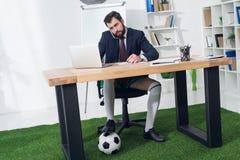 бизнесмен с футбольным мячом говоря на smartphone на рабочем месте стоковое изображение