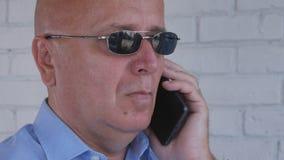 Бизнесмен с черными солнечными очками звонит телефонный звонок стоковая фотография