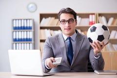Бизнесмен с шариком футбола в офисе стоковые изображения