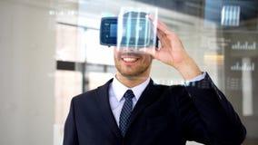 Бизнесмен с шлемофоном и кубом vr на экране