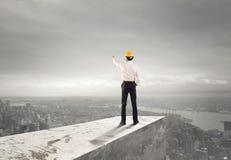 Бизнесмен с шлемом показывает правильное направление стоковое фото