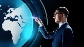 Бизнесмен с hologram земли над чернотой Стоковое Фото