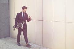 Бизнесмен с longboard и мобильным телефоном Стоковое Изображение