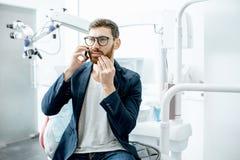 Бизнесмен с toothache в зубоврачебном офисе стоковые изображения rf