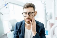 Бизнесмен с toothache в зубоврачебном офисе стоковые фотографии rf