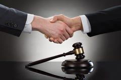 Бизнесмен тряся руки перед мушкелом Стоковое Изображение RF