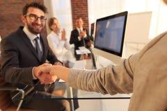 Бизнесмен тряся руки при деловой партнер сидя около вашего настольного компьютера Стоковое фото RF