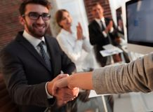 Бизнесмен тряся руки при деловой партнер сидя около вашего настольного компьютера Стоковые Изображения RF