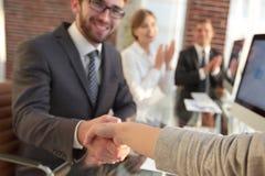 Бизнесмен тряся руки при деловой партнер сидя около вашего настольного компьютера Стоковая Фотография RF