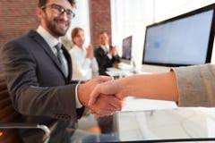 Бизнесмен тряся руки при деловой партнер сидя около вашего настольного компьютера Стоковые Изображения