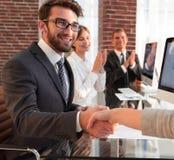 Бизнесмен тряся руки при деловой партнер сидя около вашего настольного компьютера Стоковое Изображение RF