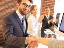 Бизнесмен тряся руки при деловой партнер сидя около вашего настольного компьютера Стоковые Фотографии RF