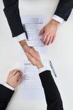 Бизнесмен тряся руки с мужским выбранным на столе Стоковые Изображения
