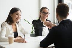 Бизнесмен тряся руку женского сотрудника во время meeti компании Стоковое фото RF