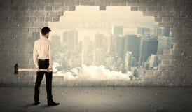 Бизнесмен ударяя стену с молотком на виде на город Стоковая Фотография