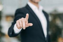 Бизнесмен указывает его палец на экран, прессы и краны стоковые изображения