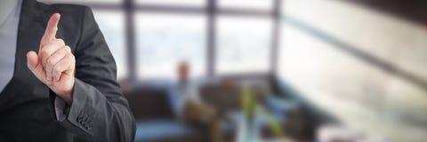 Бизнесмен указывая его палец на камеру против беспечального бизнесмена сидя на софе Стоковое Изображение