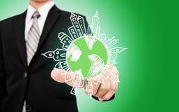 Бизнесмен указывая на глобус doodle с зданиями дружественное к Эко дело, зеленое дело, экологическое ресервирование Стоковое Изображение