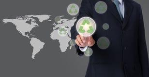 Бизнесмен указывая на зеленый цвет рециркулирует символ с предпосылкой карты мира Стоковое Фото