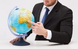 Бизнесмен указывая палец к глобусу земли Стоковые Фотографии RF