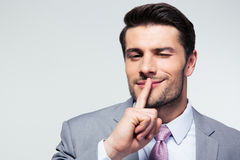 Бизнесмен указывая палец над губами, прося безмолвие стоковое фото rf