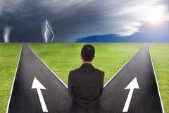Бизнесмен думая к выбору между громом и солнечным путем Стоковое Изображение