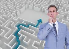 Бизнесмен думая перед белой предпосылкой с голубой стрелкой в лабиринте Стоковое фото RF