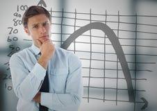 Бизнесмен думая против doodle диаграммы и расплывчатого серого офиса Стоковые Фотографии RF