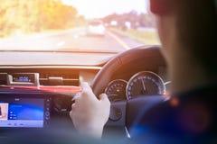 Бизнесмен управляя в его автомобиле на дороге Стоковые Фото