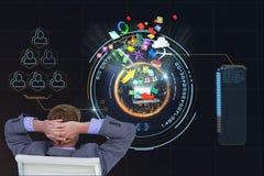 Бизнесмен усаженный на стул наблюдает цифровое изображение против черной предпосылки Стоковые Фото