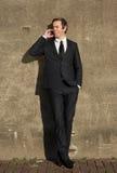 Бизнесмен усмехаясь и говоря на мобильном телефоне outdoors Стоковое Изображение