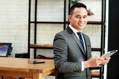 Бизнесмен усмехаясь и держа таблетку пока положитесь назад на tabl стоковое изображение