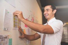Бизнесмен усмехаясь и подготавливая документы Стоковые Изображения