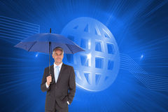 Бизнесмен усмехаясь на камере и держа голубой зонтик Стоковая Фотография RF