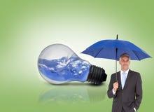 Бизнесмен усмехаясь на камере и держа голубой зонтик Стоковые Изображения