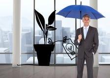 Бизнесмен усмехаясь на камере и держа голубой зонтик Стоковые Фото
