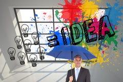 Бизнесмен усмехаясь на камере и держа голубой зонтик Стоковое Изображение
