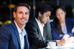 Бизнесмен усмехаясь на камере пока коллеги взаимодействуя на заднем плане Стоковое фото RF