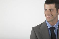 Бизнесмен усмехаясь на серой предпосылке Стоковая Фотография