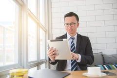 Бизнесмен усмехаясь пока использующ планшет стоковые изображения rf