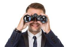 Бизнесмен усмехаясь пока использующ бинокулярное Стоковое Изображение RF