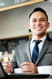 Бизнесмен усмехаясь пока работающ на его компьтер-книжке стоковое изображение