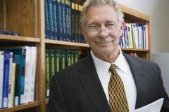 Бизнесмен усмехаясь пока стоящ в библиотеке Стоковое Изображение