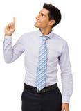 Бизнесмен усмехаясь пока указывающ вверх стоковые фотографии rf
