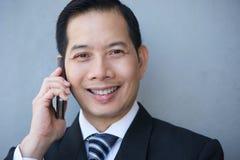 Бизнесмен усмехаясь с мобильным телефоном Стоковое фото RF