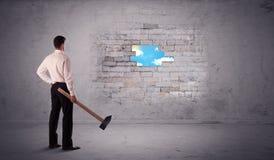 Бизнесмен ударяя кирпичную стену с молотком стоковые изображения