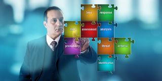 Бизнесмен фокусируя на головоломке оценки степени риска Стоковые Фотографии RF