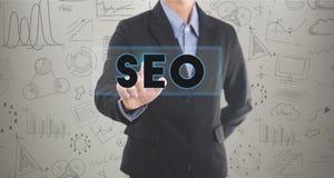 Бизнесмен формулируя отжимать рука SEO знак на виртуальном экране Стоковая Фотография RF